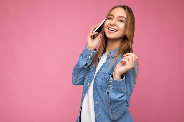 Zdjęcie pięknej uśmiechniętej szczęśliwej młodej kobiety blondynka noszącej dorywczo niebieską koszulę dżinsową na białym tle nad różowym tłem, trzymając w ręku i rozmawiając na telefonie komórkowym, patrząc na kamery