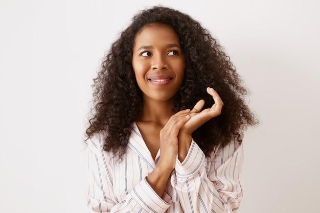 Zdjęcie pięknej, wspaniałej młodej ciemnoskórej kobiety z długimi, obszernymi włosami, podekscytowana, pełna ciekawych pomysłów, zacierająca ręce i spoglądająca z ukosa, pozująca na ścianie copyspace