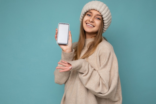 Zdjęcie piękny uśmiechnięty pozytywny przystojny młoda kobieta ubrana w stylowy beżowy sweter i beż