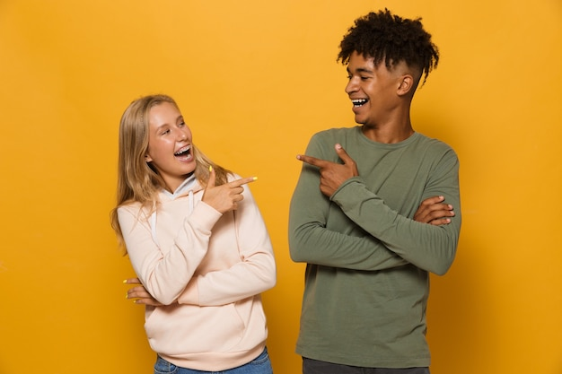 Zdjęcie pięknych studentów mężczyzny i kobiety w wieku 16-18 lat z aparatami ortodontycznymi, śmiejących się do siebie, odizolowanych na żółtym tle
