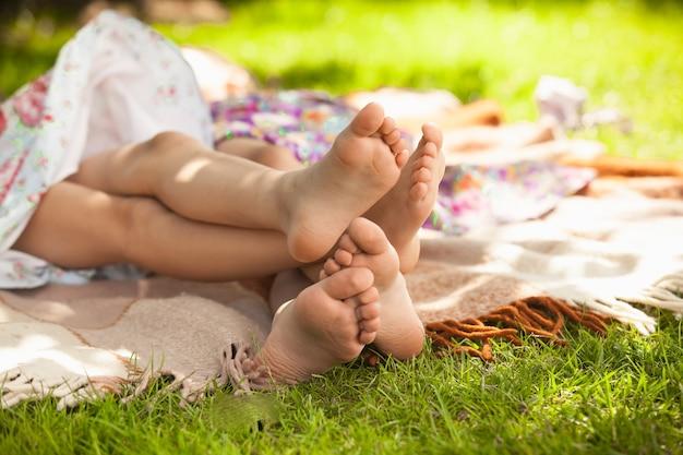 Zdjęcie plenerowe dwóch dziewczynek leżących na trawie i bawiących się