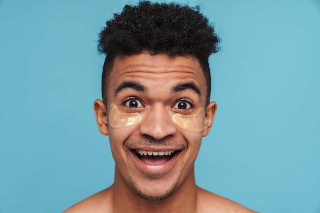 Zdjęcie podekscytowanego afroamerykanina z łatami pod oczami uśmiechniętym na niebieskim tle