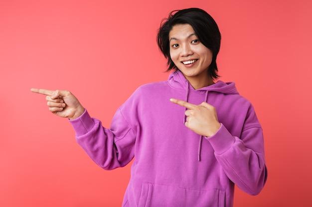Zdjęcie podekscytowanego azjatyckiego faceta w bluzie, radującego się i wskazującego palcami na copyspace na białym tle nad czerwoną ścianą