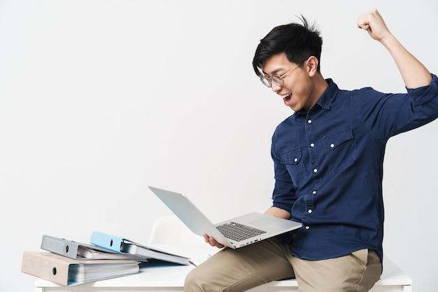 Zdjęcie podekscytowanego azjatyckiego mężczyzny noszącego okulary siedzącego przy stole i pracującego na laptopie w biurze na białym tle nad białą ścianą