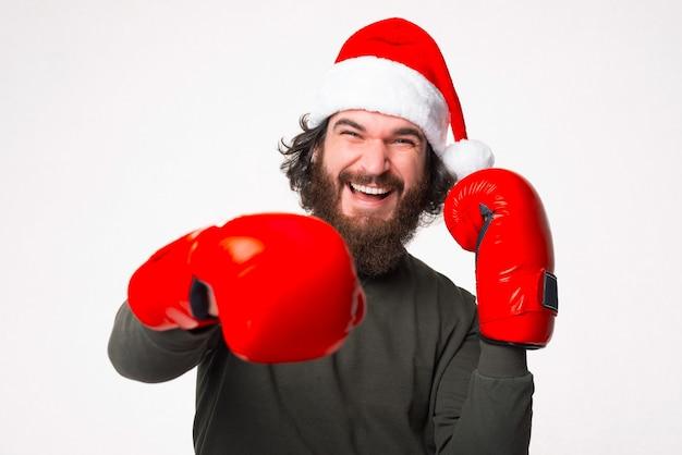 Zdjęcie podekscytowanego brodatego mężczyzny w kapeluszu świętego mikołaja, który uderza pięścią w czerwone rękawice bokserskie