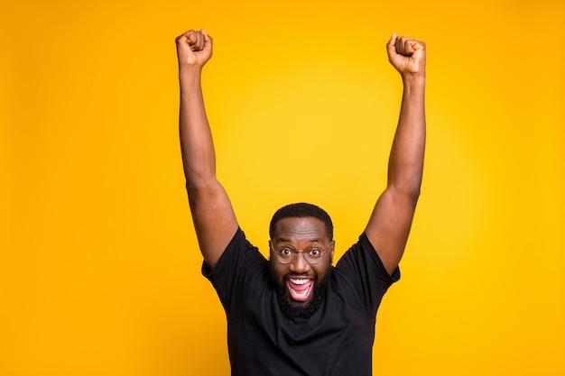 Zdjęcie podekscytowanego, uszczęśliwionego radującego się mężczyzny wyrażającego szalone emocje na twarzy w okularach unoszących pięści do góry po wygraniu biletów na wyjazd za granicę na wakacje odizolowany żywy kolor żółta ściana