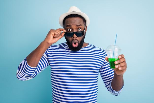 Zdjęcie podekscytowanego, zszokowanego ciemnoskórego faceta podróżnika trzymającego zielony alkoholowy kubek z napojem zdejmującego specyfikacje patrz atrakcyjna dziewczyna nosi białą czapkę przeciwsłoneczną pasiastą marynarską koszulę na białym tle niebieski kolor ściana