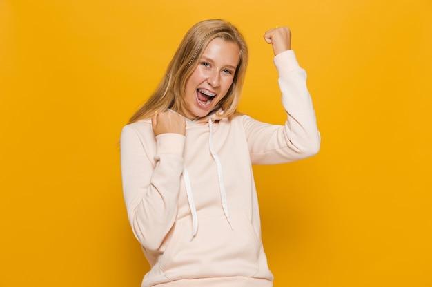 Zdjęcie podekscytowanej dziewczyny 16-18 lat z aparatami ortodontycznymi zaciskającymi pięści, odizolowane na żółtym tle
