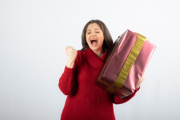 Zdjęcie podekscytowanej dziewczyny trzymającej w ręku prezent na boże narodzenie.