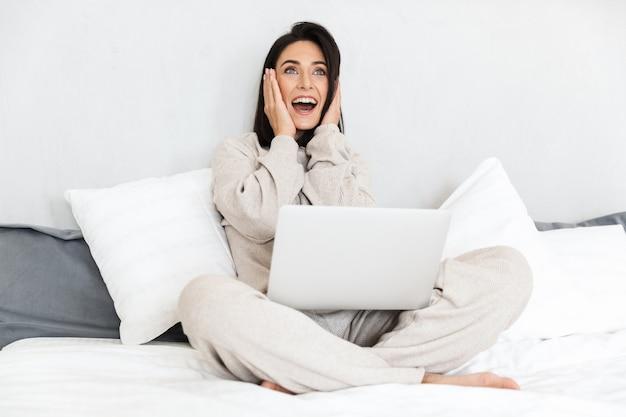 Zdjęcie podekscytowanej kobiety 30-latki korzystającej z laptopa, siedzącej na łóżku z białą pościelą w przytulnym mieszkaniu