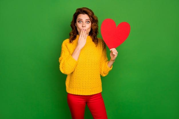 Zdjęcie podekscytowanej pani trzymaj papierową pocztówkę w kształcie serca ukryj usta nie wierzę przystojny facet zaprosił ją na randkę nosić żółty sweter z dzianiny czerwone spodnie na białym tle zielony kolor ściana