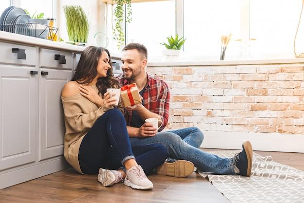 Zdjęcie podekscytowanej pary brunetka mężczyzna i kobieta 20s śniadanie w mieszkaniu, siedząc na podłodze z pudełko. świętujemy wakacje.