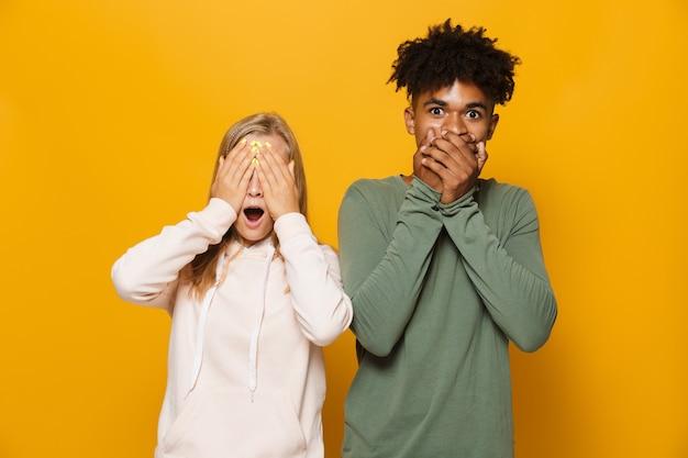 Zdjęcie podekscytowanej pary mężczyzny i kobiety 16-18 lat z aparatami ortodontycznymi zakrywającymi twarze rękami, odizolowane na żółtym tle