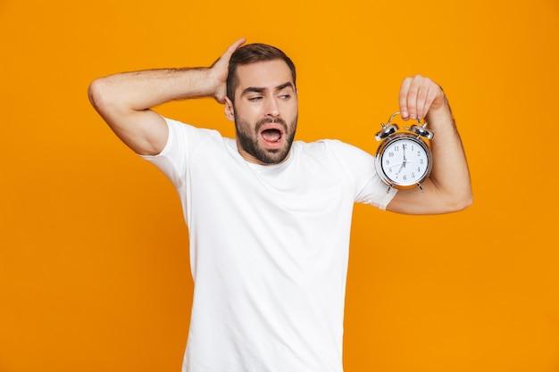 Zdjęcie poirytowanego mężczyzny 30s w codziennym noszeniu, trzymając budzik, na białym tle