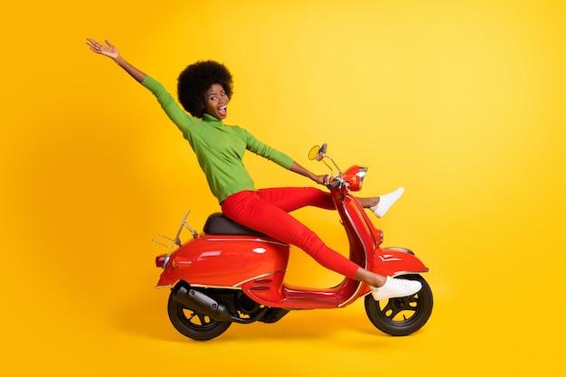 Zdjęcie portret afroamerykańskiej kobiety jadącej na rowerze machająca ręką z rozłożonymi nogami otwartymi ustami na żywym żółtym kolorowym tle
