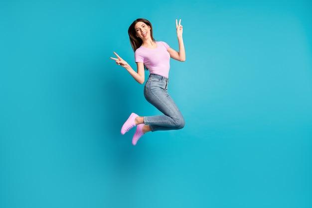 Zdjęcie portret błyszczącej słodkiej dziewczyny nosi dorywczo fioletową koszulkę skacząc pokazując znak v na białym tle w kolorze niebieskim