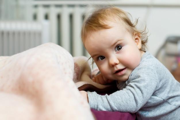 Zdjęcie portret dziewczynki z różowymi policzkami. dziecko wstaje na nogi