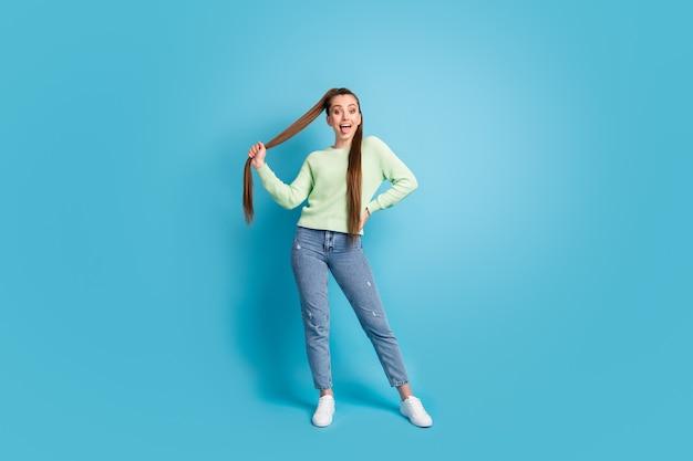 Zdjęcie portret dziewczyny pokazującej język trzymający włosy na białym tle na pastelowym niebieskim tle
