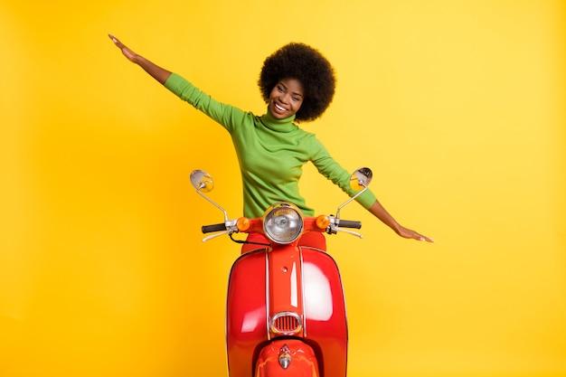 Zdjęcie portret funky figlarnej kobiety prowadzącej rower, dzięki czemu samolot rozciągający ramiona izolowane na żywym żółtym kolorowym tle