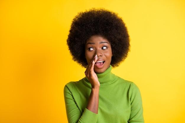 Zdjęcie portret kobiety dzielącej się tajemnicą trzymającą rękę w pobliżu ust na żywym żółtym kolorowym tle