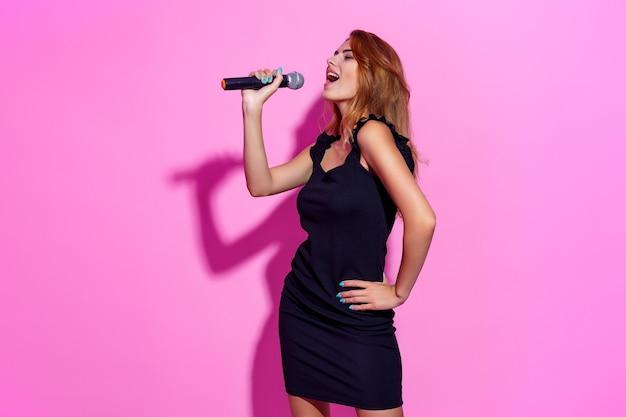 Zdjęcie portret kobiety trzymającej mikrofon w rękach na białym tle na pastelowym różowym tle