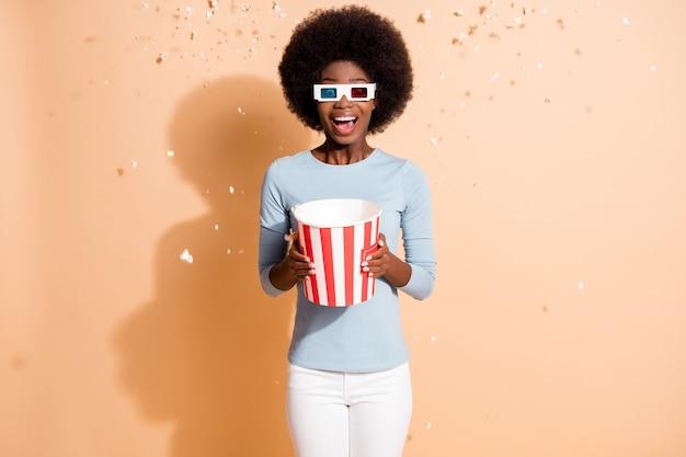 Zdjęcie portret kręcone podekscytowany zdumiony ciemna skóra dziewczyna trzyma pudełko z popcornem latającym w powietrzu oglądając film w okularach 3d na białym tle na beżowym kolorze