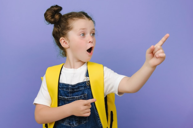 Zdjęcie portret małej brunetki w okularach wskazującej na puste miejsce na dłoni śmiejącej się na jasnym fioletowym tle