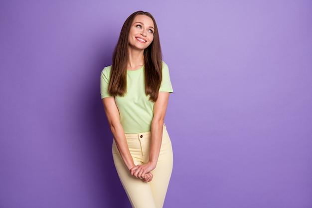Zdjęcie portret marzycielskiej dziewczyny z rękami opuszczonymi na żywym fioletowym tle