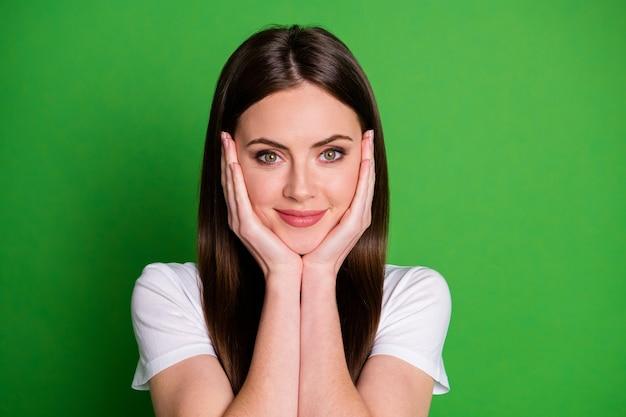 Zdjęcie portret młodej kobiety dotykającej policzków twarzy dwiema rękami na żywym zielonym kolorowym tle