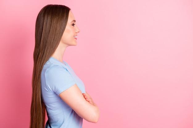 Zdjęcie portret profil kobiety ze skrzyżowanymi rękami patrzącej na pustą przestrzeń na pastelowym różowym kolorowym tle