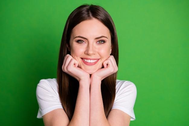 Zdjęcie portret szczęśliwej dziewczyny dotykającej policzków twarzy rękami odizolowanymi na żywym zielonym kolorowym tle