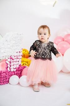 Zdjęcie portret urodzinowej dziewczyny 1 rok w różowej sukience z różowymi balonami. dziecko na wakacjach uśmiecha się, dziecięce emocje. przyjęcie urodzinowe