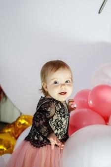 Zdjęcie portret urodzinowej dziewczyny 1 rok w różowej sukience z różowymi balonami. dziecko na wakacjach uśmiechy, dziecięce emocje. przyjęcie urodzinowe
