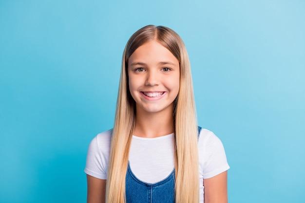 Zdjęcie portret uśmiechniętej uczennicy odizolowanej na pastelowym niebieskim tle