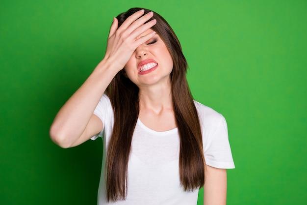 Zdjęcie portret wściekłej kobiety zakrywającej twarz ręką facepalming na żywym zielonym kolorowym tle