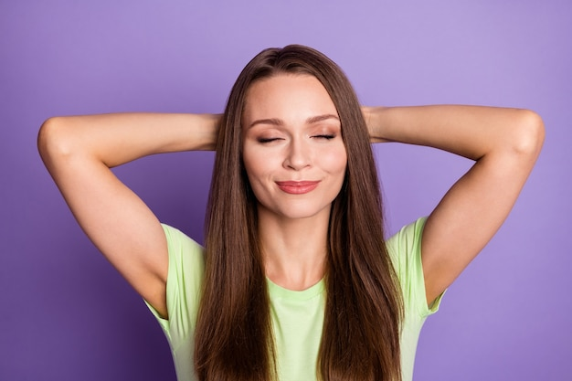 Zdjęcie portret zachwyconej dziewczyny z zamkniętymi oczami, ręce za plecami na żywym, fioletowym tle
