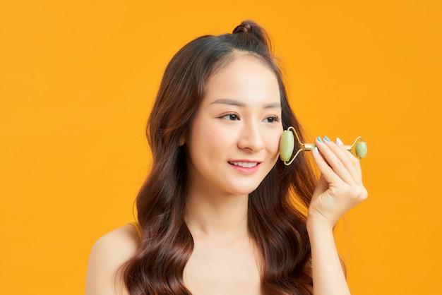 Zdjęcie portretowe młodej kobiety wyglądającej na zrelaksowaną podczas korzystania z naturalnego kwarcowego wałka do twarzy.