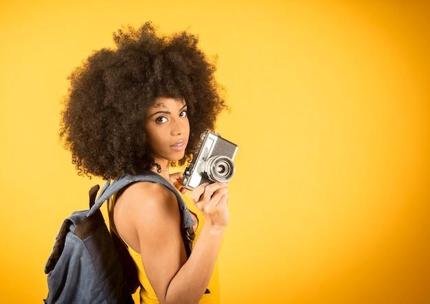 Zdjęcie portretowe pięknej kręconej, mieszanej czarnej skóry dziewczyny, biorąc selfie w parku, uśmiechając się, machając z dorywczo koszulowym plecakiem na żółtym tle