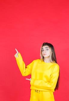 Zdjęcie portretowe piękny model dziewczyny stojącej i wskazując na bok