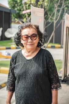 Zdjęcie portretowe pięknych starszych kobiet z azji noszących okulary przeciwsłoneczne z pięknymi włosami