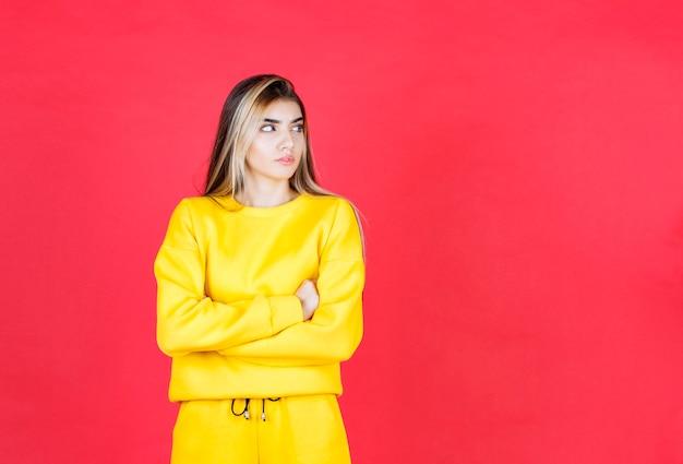 Zdjęcie portretowe poważnego modelu dziewczyny stojącej i pozowanie ze skrzyżowanymi rękami