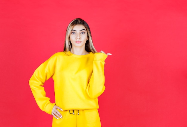 Zdjęcie portretowe poważnego modelu dziewczyny stojącej i wskazując na bok