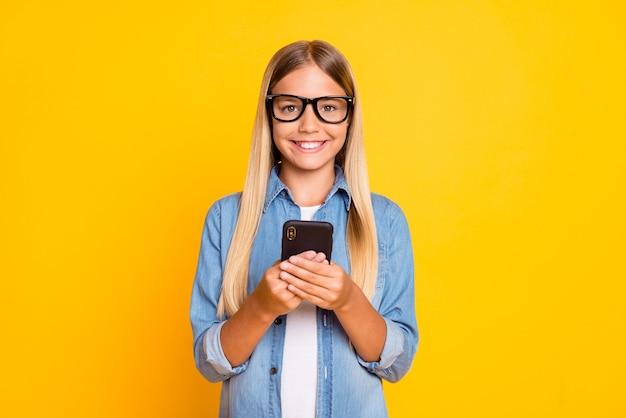 Zdjęcie portretowe preteen uczennicy z dużymi okularami uśmiecha się, trzymając telefon komórkowy za pomocą mediów społecznościowych na jasnożółtym tle