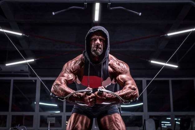 Zdjęcie potężnego sportowca w bluzie z kapturem, ćwiczącego w crossoverze na siłowni. koncepcja fitness i kulturystyki. różne środki przekazu