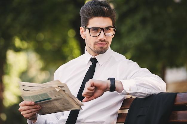 Zdjęcie poważnego biznesmena w garniturze, czytanie gazety na ławce w zielonym parku i patrząc na zegarek