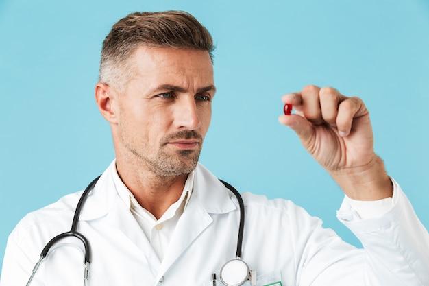 Zdjęcie poważnego lekarza na sobie biały fartuch, trzymając w ręku jedną tabletkę, stojąc na białym tle nad niebieską ścianą