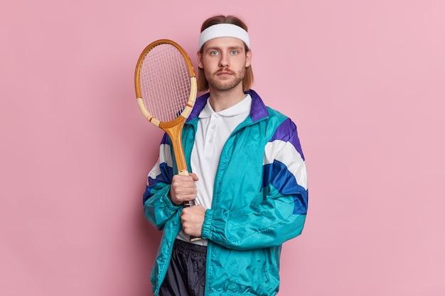 Zdjęcie poważnego mężczyzny trzymającego rakietę tenisową wygląda na pewnego siebie ubranego w sportową odzież i chwali się swoimi osiągnięciami sportowymi, praktykami tenisowymi osiągniętymi na najwyższym poziomie. zwycięzca meczu.
