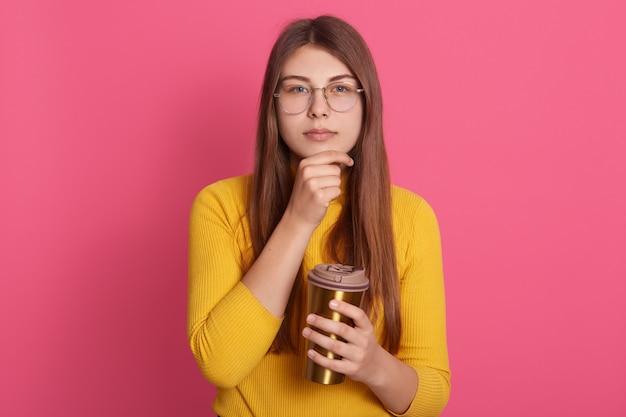 Zdjęcie poważnego młodego modelu gospodarstwa kubek z napojem, patrząc bezpośrednio o zamyślonym wyrazie twarzy