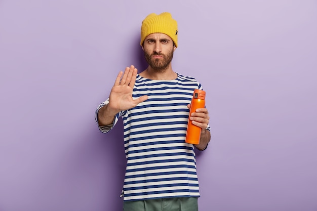 Zdjęcie poważnego niezadowolonego mężczyzny pokazuje znak odmowy, wykonuje gest stopu dłonią trzyma termos pije herbatę w domu, nie ma ochoty na śniadanie. ludzie