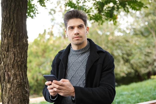 Zdjęcie poważnego przystojny młody człowiek w odzieży casual spaceru na świeżym powietrzu w zielonym parku przy użyciu telefonu komórkowego słuchania muzyki przez słuchawki.